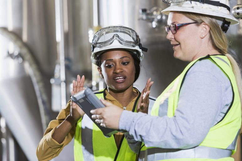 Two multiracial women working together in a manufacturing plant, standing in front of steel storage tanks.  They are wearing white hardhats with safety goggles, and yellow reflective vests, looking at the screen of a digital tablet.  The African American woman is talking and gesturing.